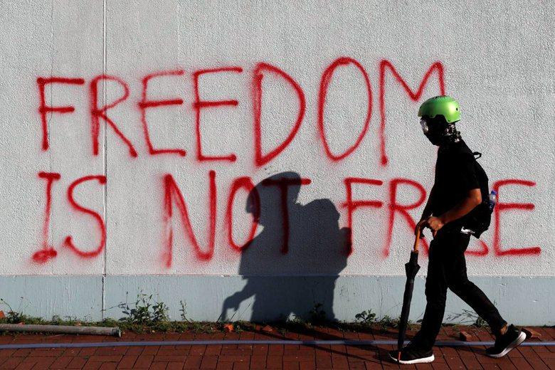 一名示威者經過一面寫著「 Freedom is not free」的牆面。 圖/...
