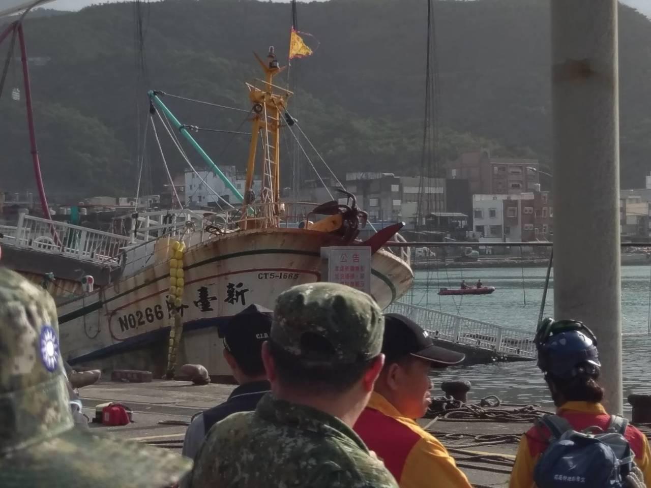 國防部說,2艘海軍拖駁船今天下午協助拖駁被壓住的漁船,目前一艘已成功拖出。圖/國...