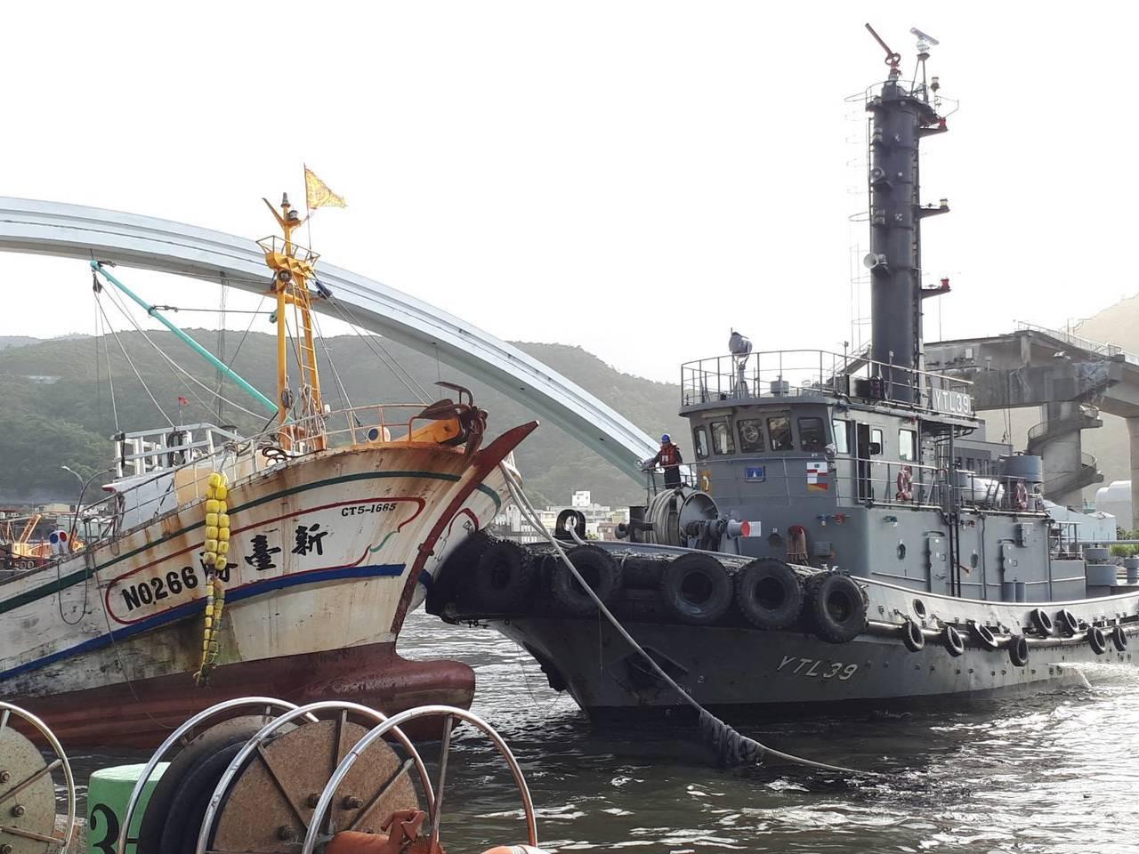 海軍蘇支部的港勤拖船,將被斷橋壓住的「新臺勝」號漁船拖出。圖/國防部提供