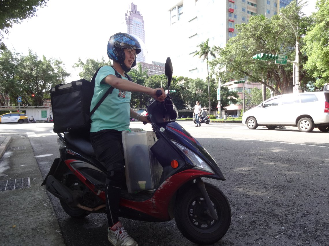 機車腳踏板上的塑膠箱,是張佑丞的「餐桌」。(圖:記者林信男攝)