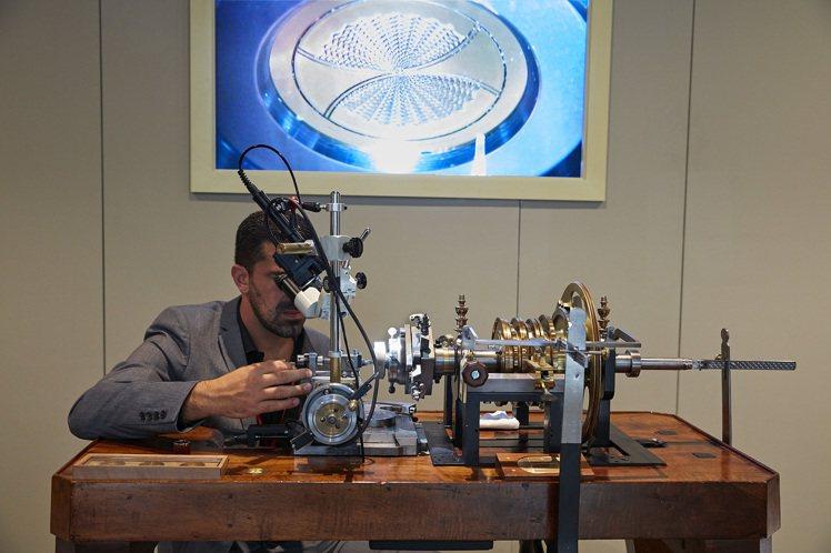 機械雕刻師的工作情境,背後螢幕是他正在雕刻的錶盤。圖/百達翡麗提供