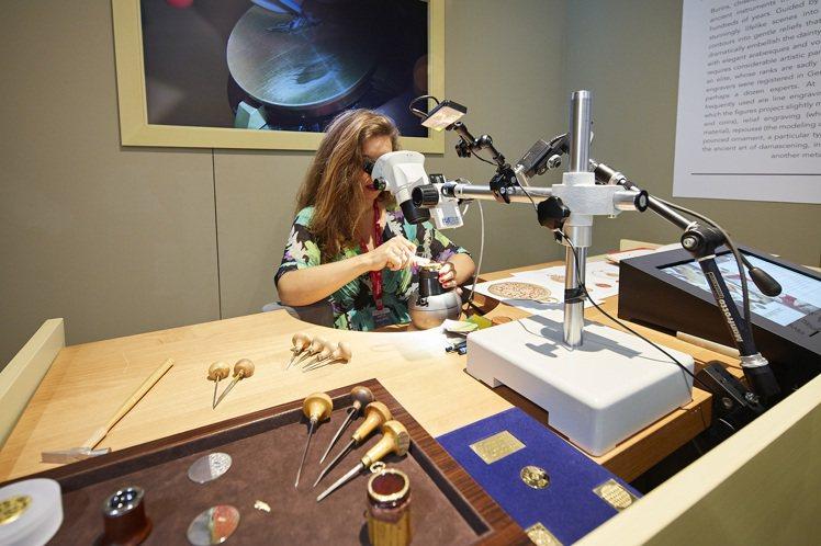 美女金雕師正在雕刻一隻小鳥,小鳥在背後螢幕上可見。圖/百達翡麗提供