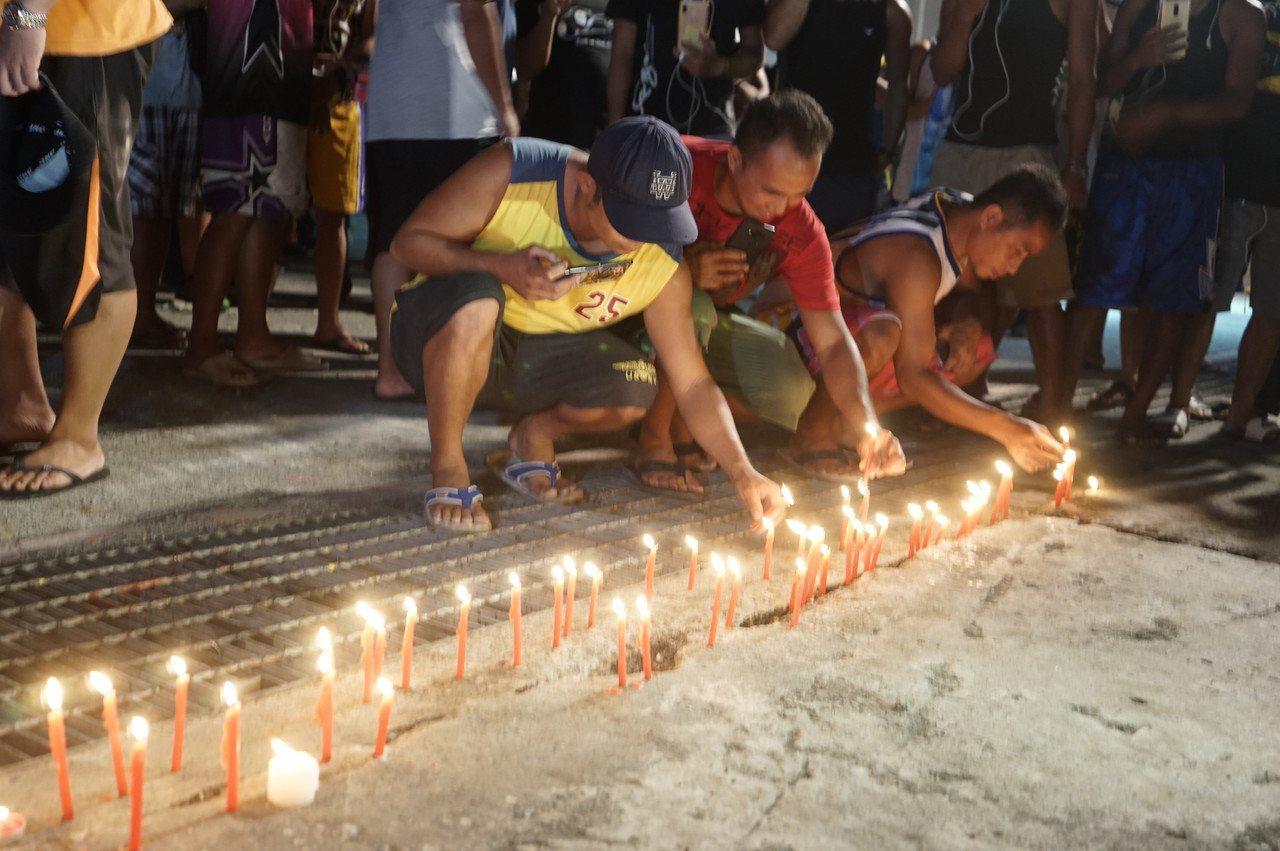 數十名外籍移工今晚到南方澳大橋事故處,用溫暖燭光,呼喚最後一名失蹤者早日回來。記...