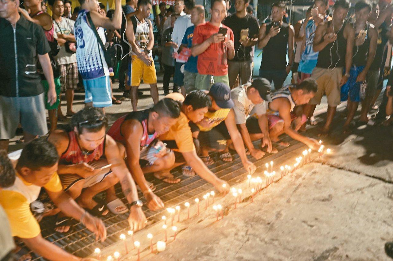 秉燭祈福一群外籍漁工昨晚到南方澳大橋斷橋邊秉著燭光,為死難者祈福。 記者王燕...
