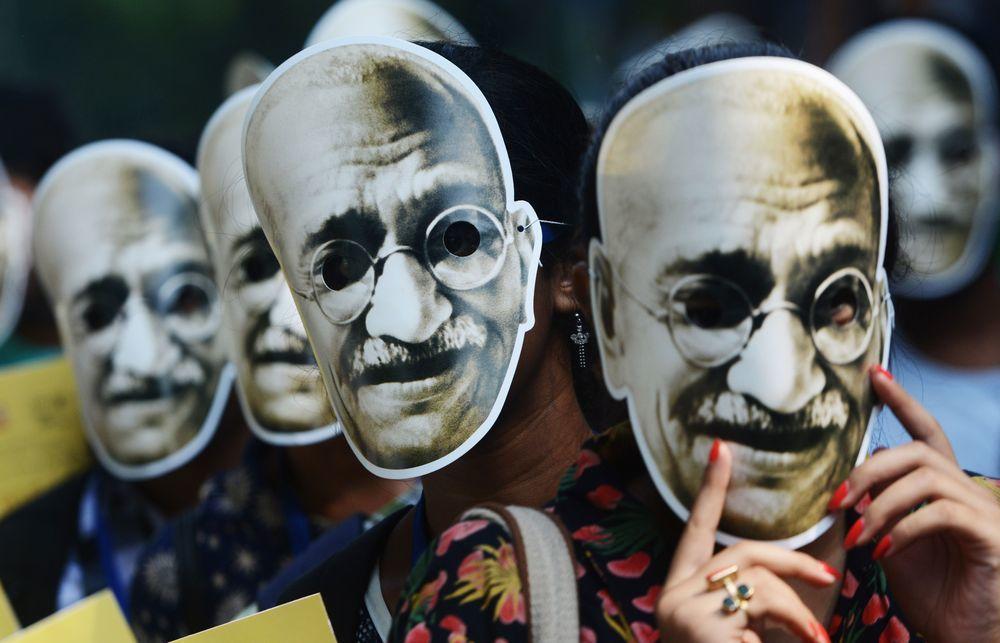 印度民眾於2日在加爾各答的遊行中,戴上聖雄甘地的面具慶祝他150歲冥誕。(法新社...
