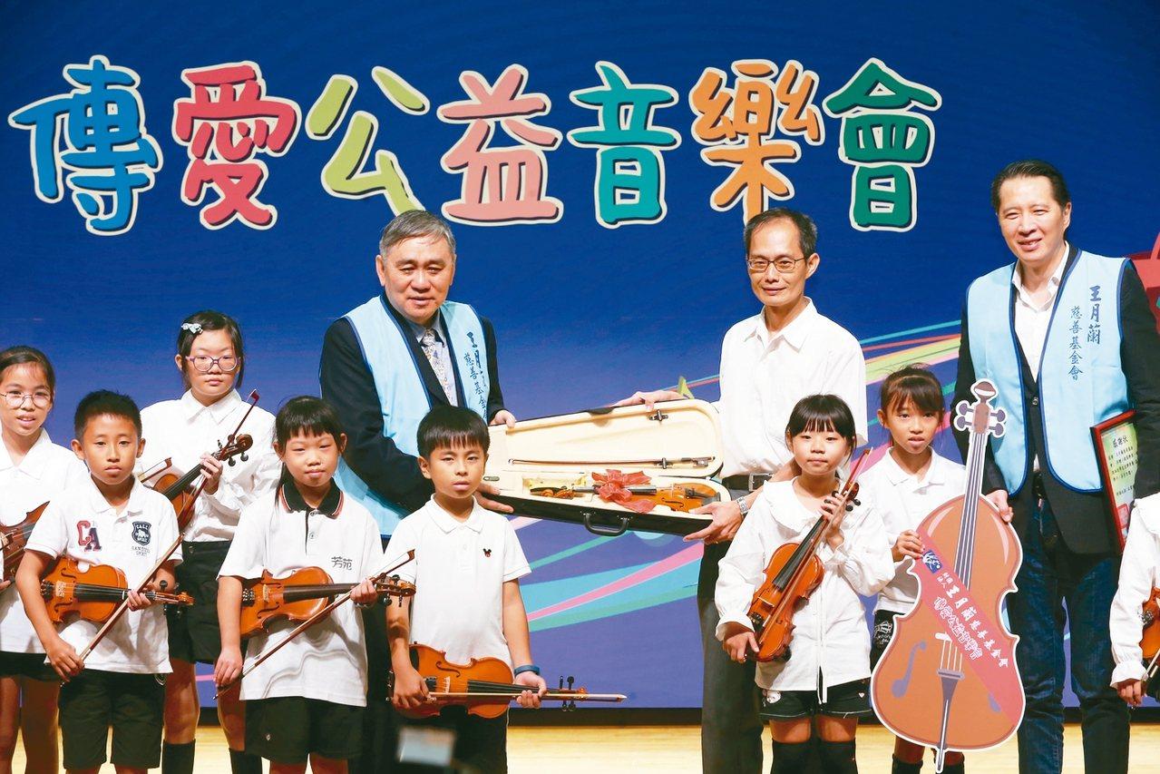 王月蘭基金會董事長王文洋(後排左三)贈送樂器給彰化芳苑國小。 記者徐兆玄/攝影