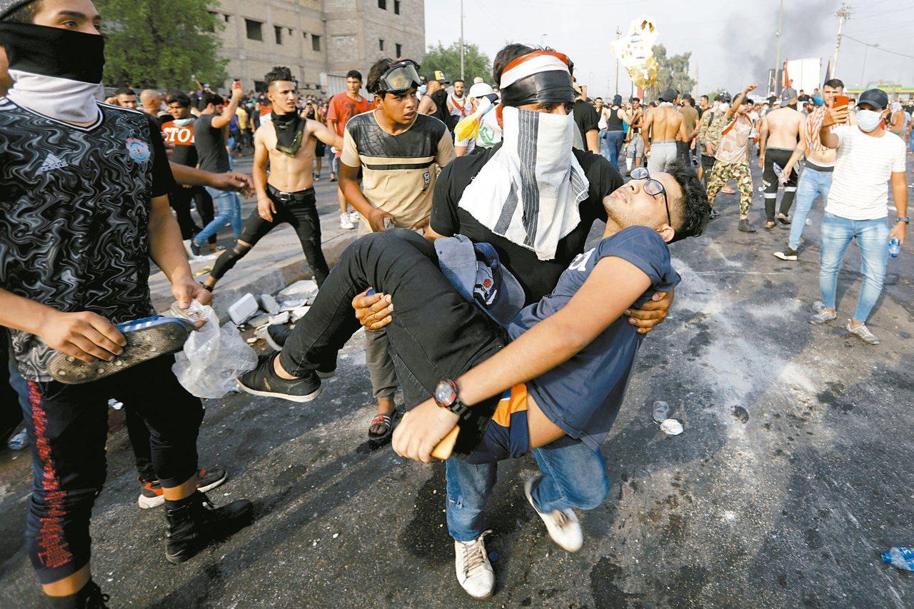 伊拉克2日發生更多抗議,24小時內死亡增加到九人。圖為示威中的傷者被同伴抱離現場...