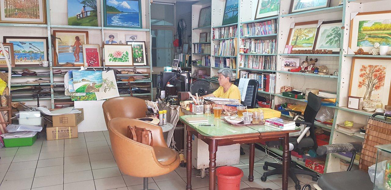 82歲的鄭夙良在自家店面裡打電腦寫作。圖/修瑞瑩攝影