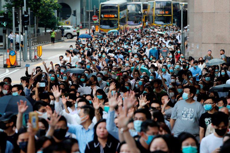 香港行政長官林鄭月娥下午公布引用《緊急法》以訂立《禁蒙面法》之決定。帶著口罩的抗議民眾今天中午在中環遊行。圖/路透