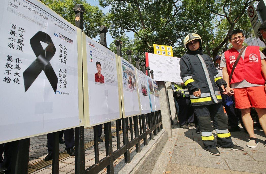 敬鵬大火後,消防員工會代表將罹難同袍的照片與新聞貼在內政部外的圍籬上班,表達訴求...