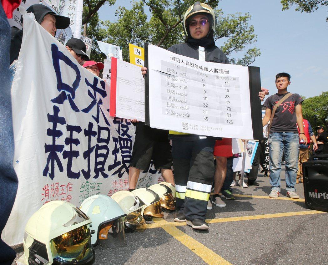 敬鵬大火後消防員發動遊行,消防員工會代表帶著六頂象徵罹難同袍的消防帽抗議。圖/聯...