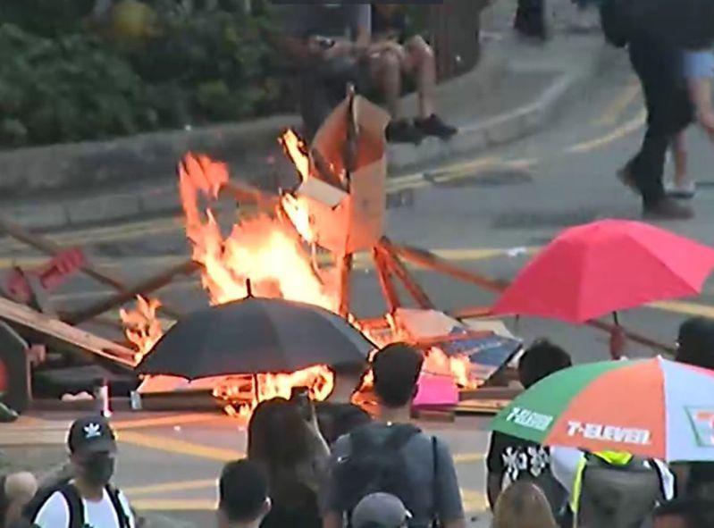 晚間近6時,示威者在中環將雜物放在大陸國慶橫額上一起焚燒。圖/取自星島日報網站