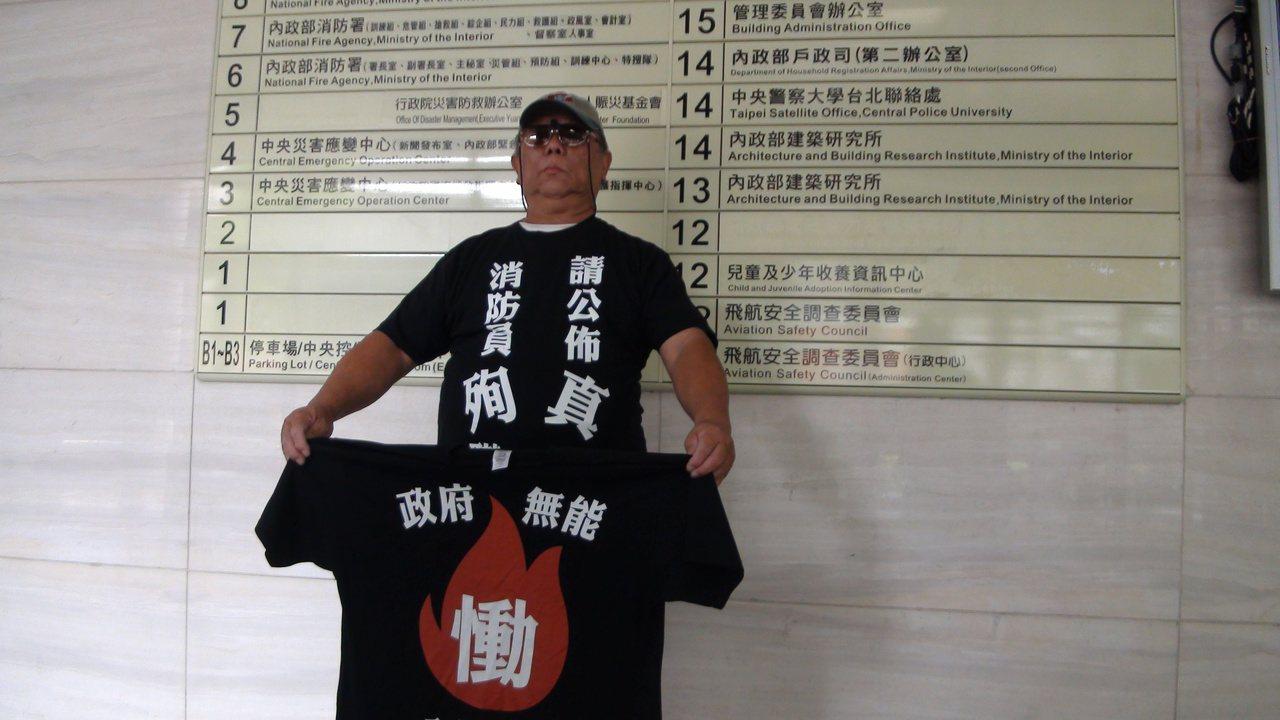 穿著黑色T恤上印有「消防員殉職,請公布真相」和「政府無能,全民監督」字樣的王石明...