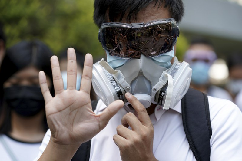 1名戴防毒面具的香港示威者4日舉起5隻手指象徵對港府的5大訴求。美聯社