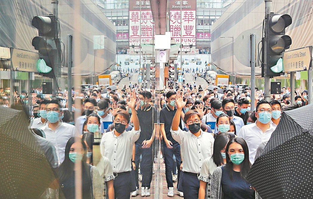港府宣布「禁蒙面法」後,許多市民紛紛戴上口罩走上街頭聚集,並高喊口號。 歐新社