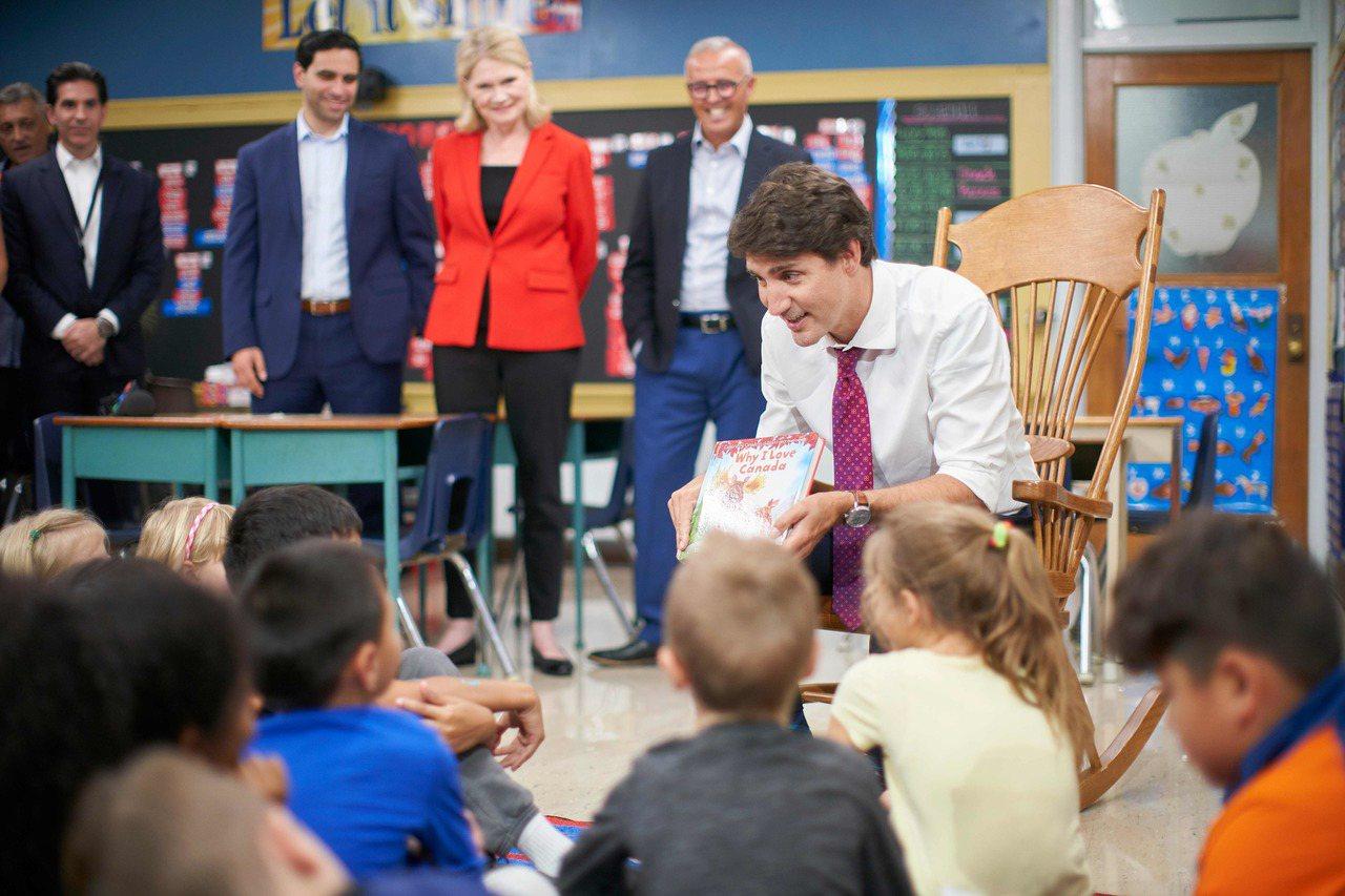 杜魯多形象親民。圖為他競選時,為學童朗讀故事書。(法新社)
