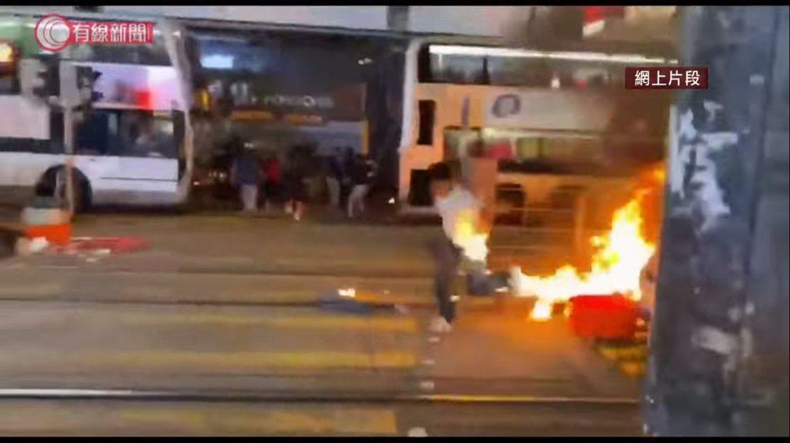 被汽油彈打中後,該名員警一度因為緊張,而把手中的手槍甩到地上,現場也有民眾衝向前...