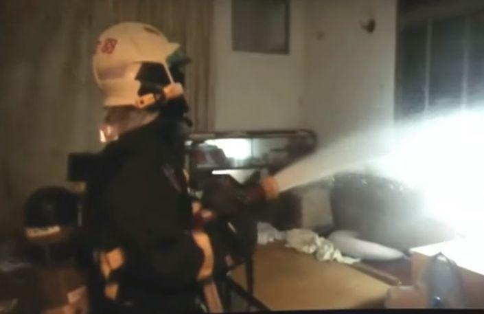 9月30日晚上,嘉義市某棟公寓火警,消防人員拉水線滅火,火苗在窗外,朝窗子射水撲...