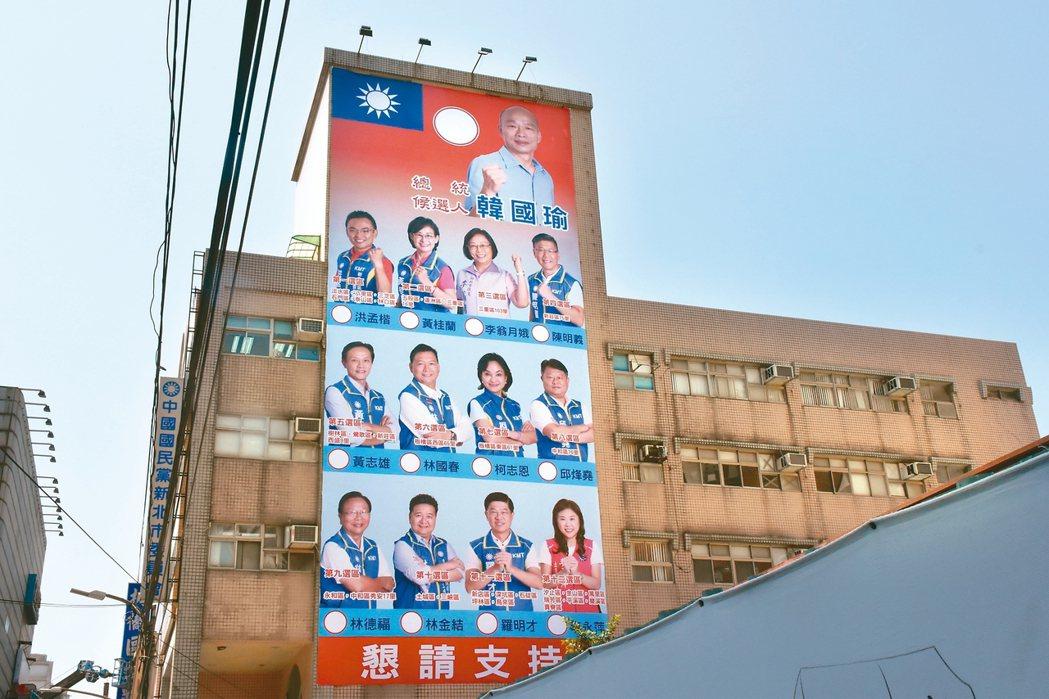 國民黨新北黨部昨天在黨部外牆掛上12位選區立委參選人與國民黨總統參選人韓國瑜的競...