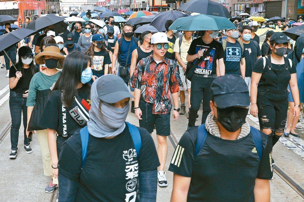 不少香港民眾無懼恐面臨ㄧ年刑期的罰則,在昨天「禁蒙面法」正式生效首日,刻意戴上口...