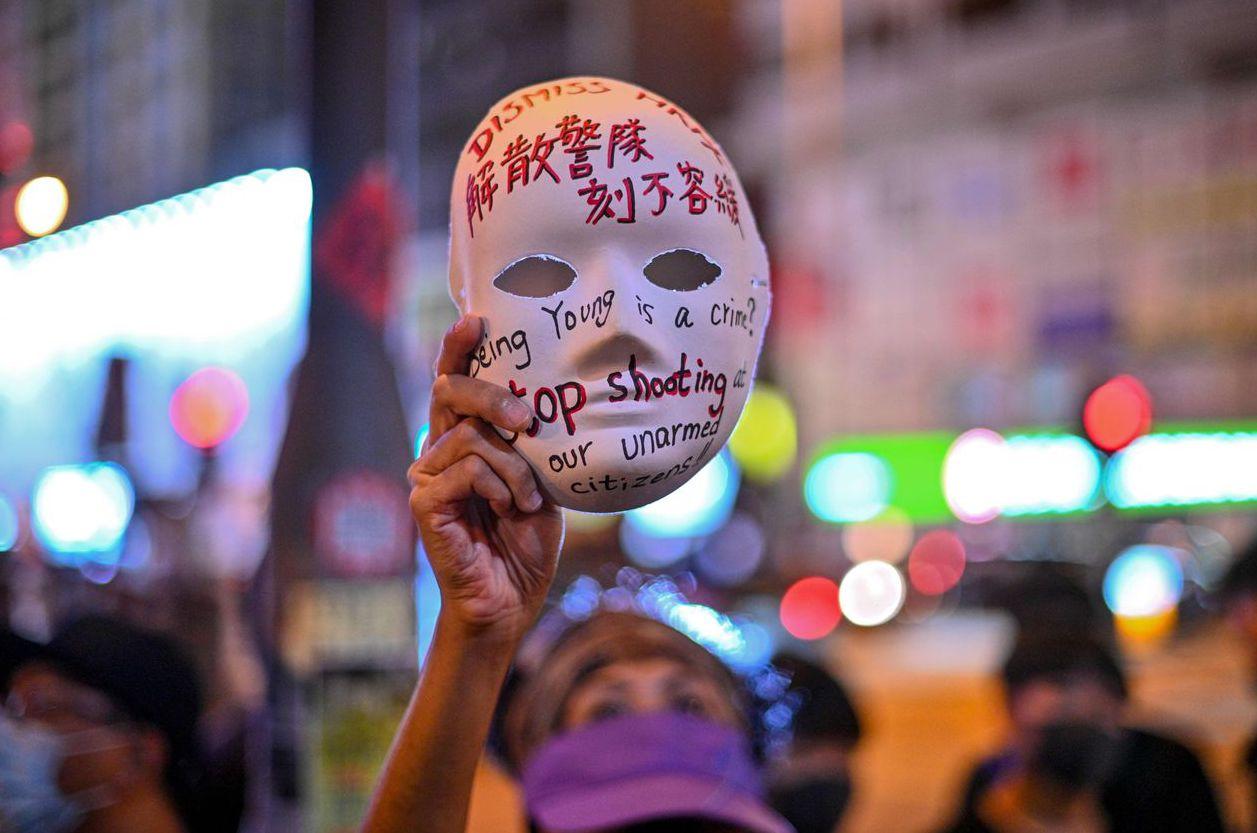 港府公布「禁蒙面法」,一名婦人高舉寫著「解散警隊 刻不容緩」的面具抗議。 (法新...