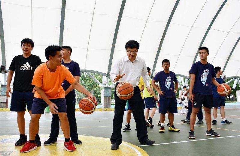 高醫大校長鐘育志脫下西裝外套,和六龜高中及寶來國中學生們一起打球。圖/高醫大提供