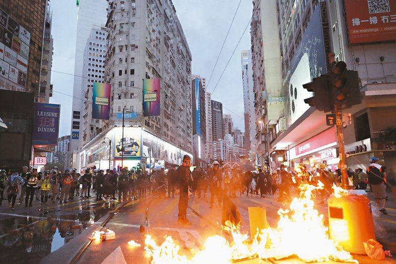 香港民眾上街遊行,有示威者向警方丟汽油彈及在街頭縱火。 (美聯社)