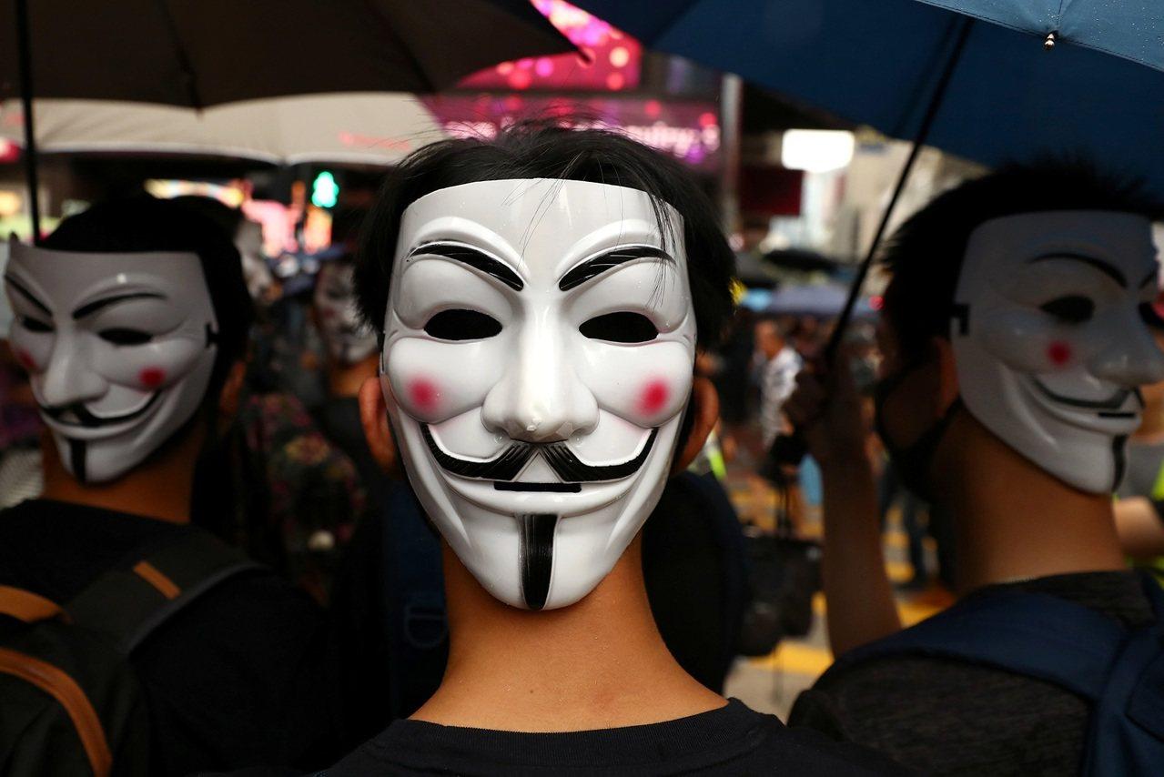 港人遊行抗議《禁蒙面法》,港警投擲催淚彈、準備水砲車戒備。路透社