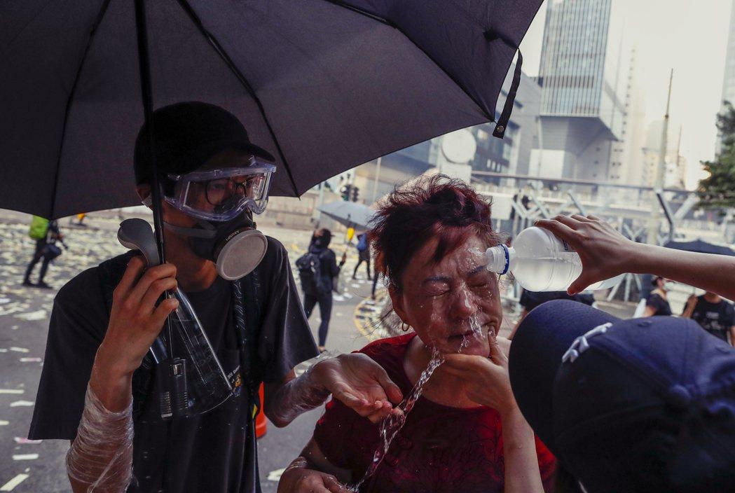 圖為10月1日,一名香港市民受到催淚彈波及,示威者幫助初步處理。 圖/美聯社