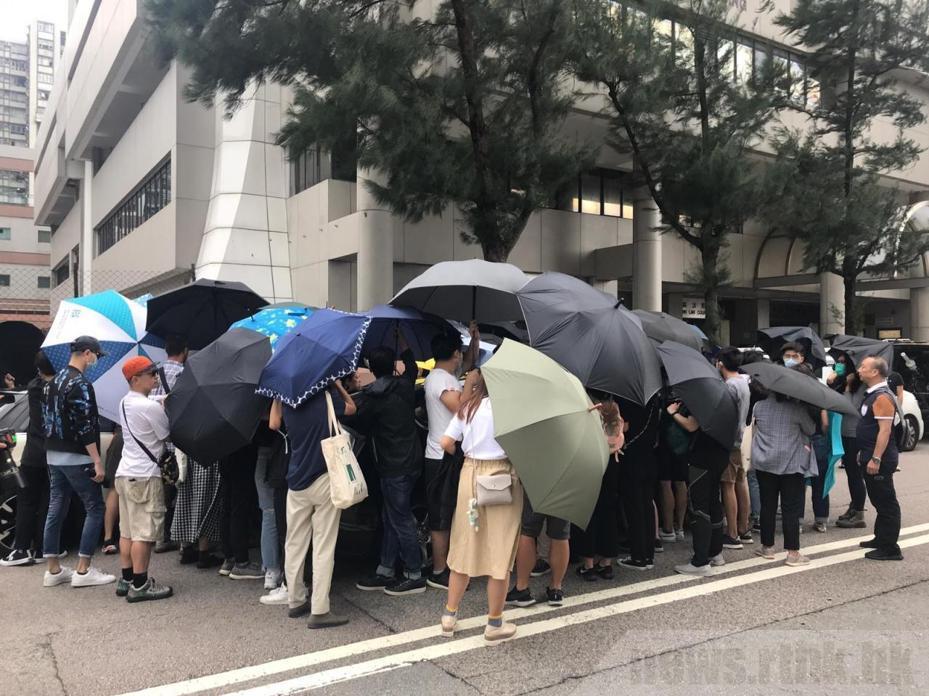 兩名被告離開法院時,有大批聲援人士舉起傘陣協助離開。取自香港電台