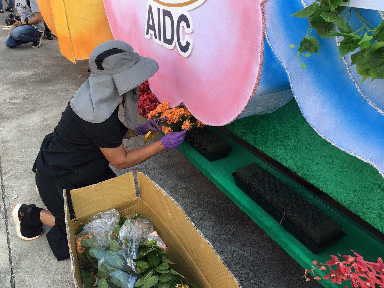 許多工作人員全副武裝戴著遮陽帽跟墨鏡,在烈日下趕工裝飾花車。記者吳姿賢/攝影