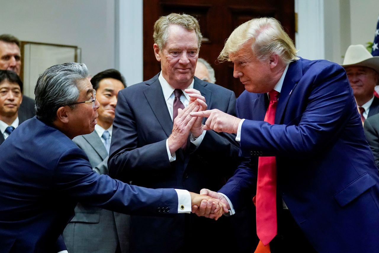 川普在白宮主持在美日貿易協定最終文本簽署儀式上,與日本駐美大使杉山晉輔握手。中為...
