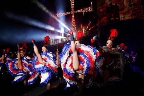 10月6日,舞者在紅磨坊最具象徵性的紅風車前跳著康康舞,慶祝成立130周年。 圖...