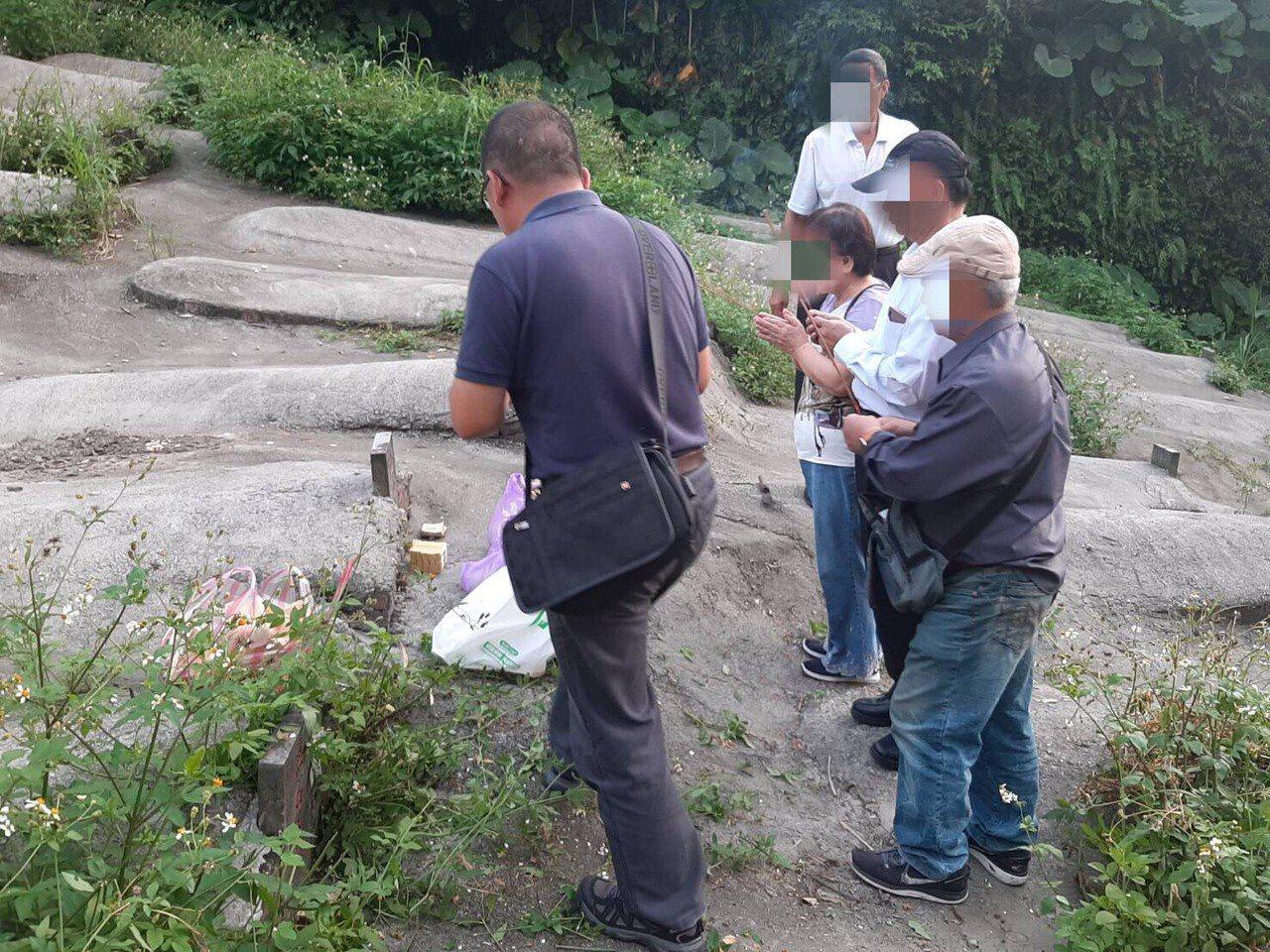 基隆警一分局三組組長許耀彬(左一)帶家屬到南榮公墓無主墓區,前往「編號A046無...