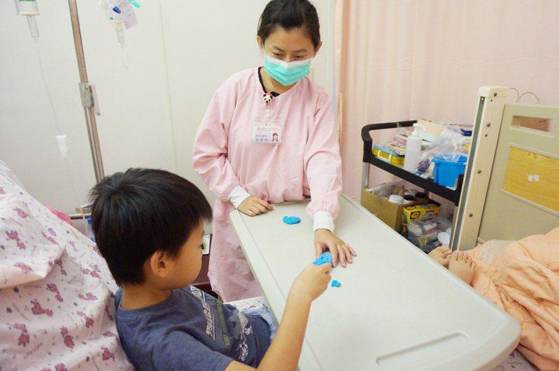 小智(化名)經由醫術治療師引導,正在體驗捏黏土的觸感及樂趣。圖/新竹馬偕醫院提供