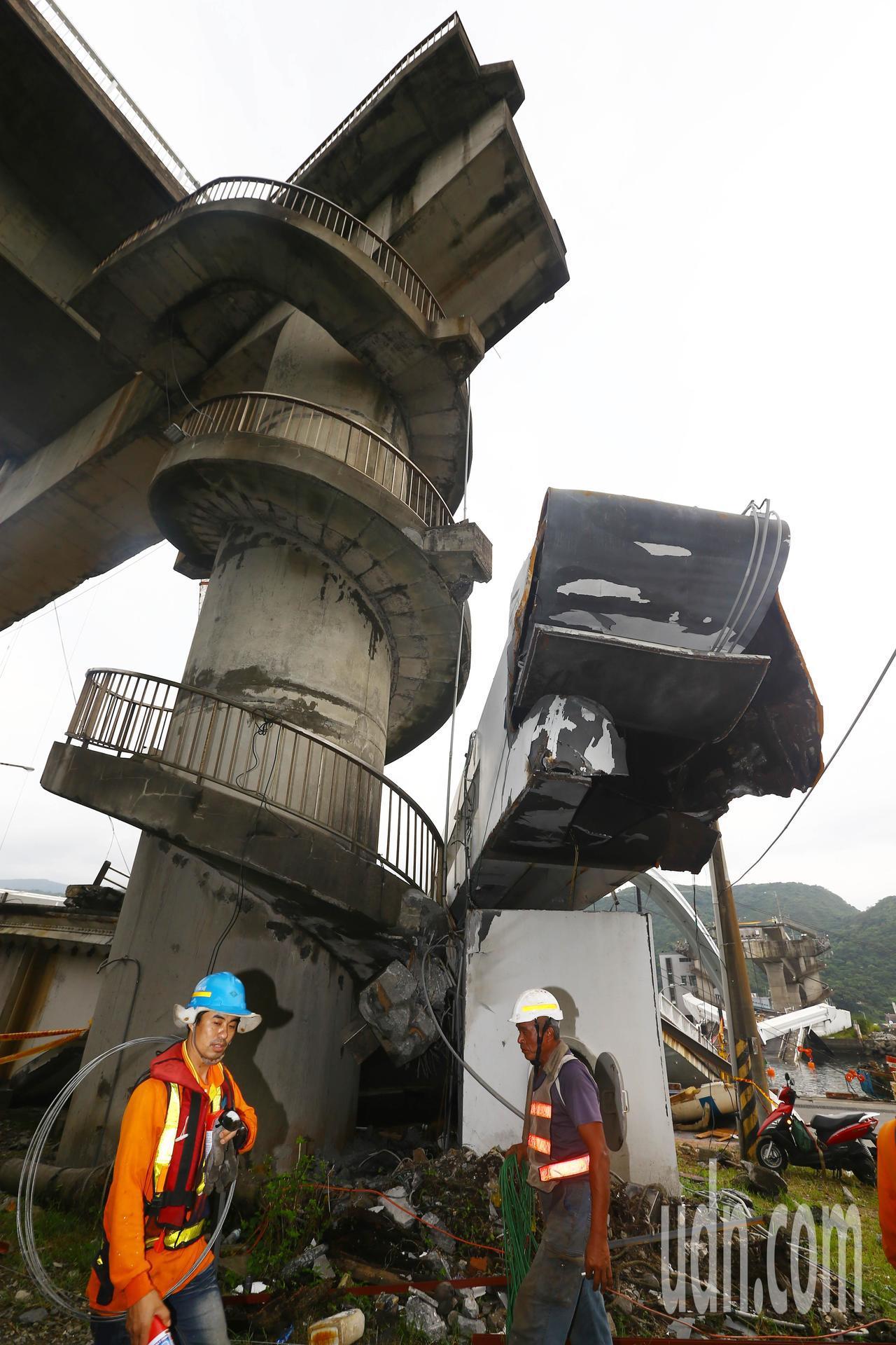 宜蘭南方澳大橋拆除作業因大雨干擾,吊掛作業往後延,施工人員來回穿梭檢查。記者杜建...