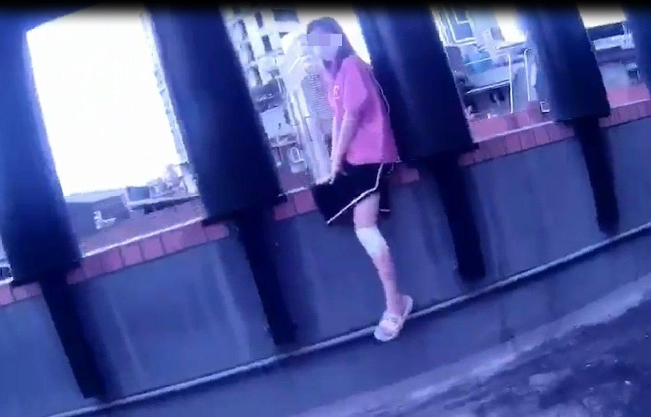 一名年輕女子今天近中午跨坐在新北市板橋區一棟大樓6樓樓頂女兒牆上意圖輕生,員警會...