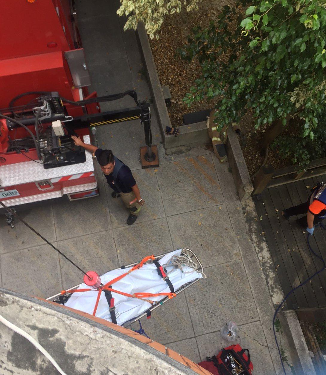 消防隊員趕至將屍體吊掛至1樓,交由警方後續處置。記者謝進盛/翻攝