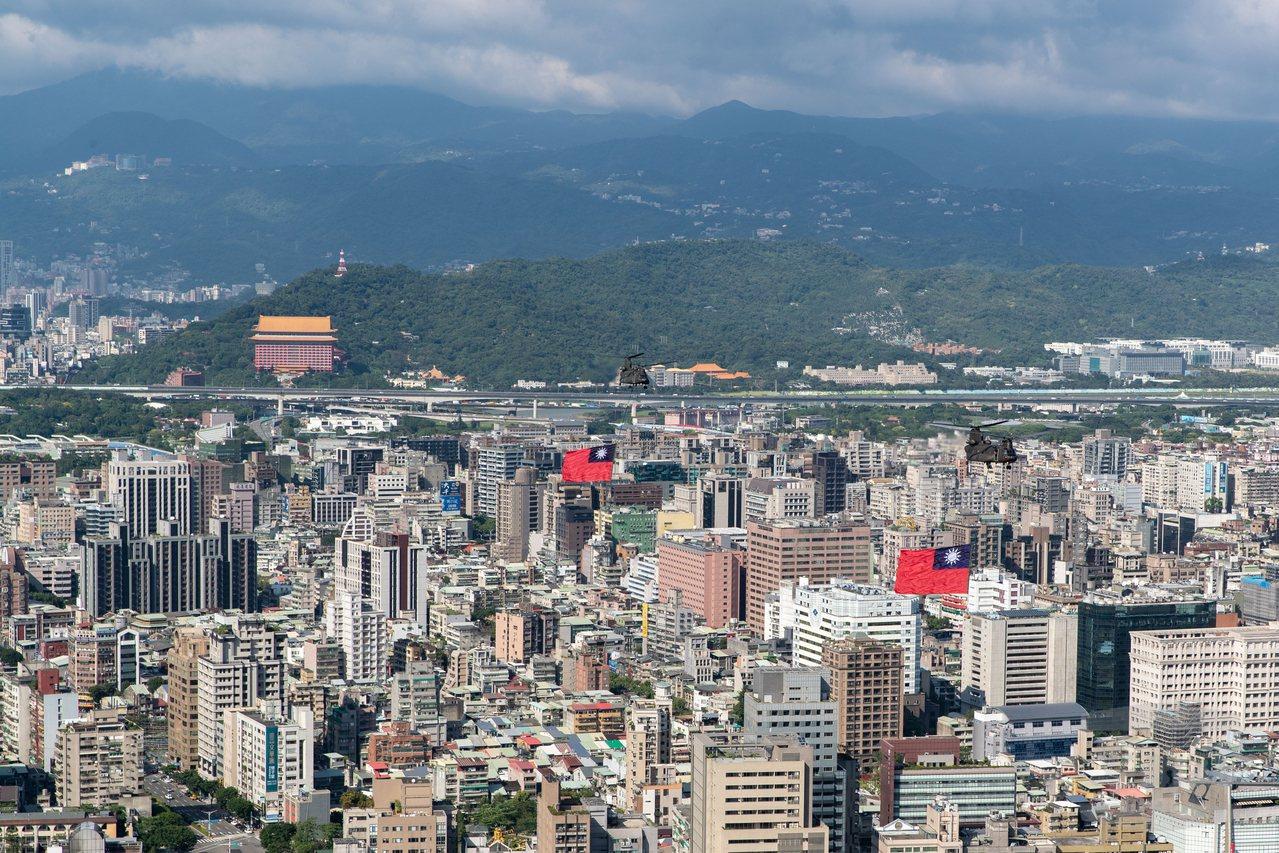 從245公尺高的新光三越站前大樓頂,「俯瞰」陸航CH-47吊掛國旗飛過市區上空。...