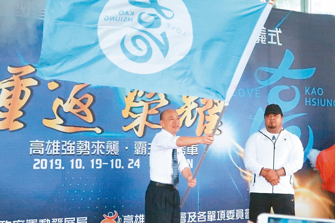 高雄市政府昨天在四維行政中心進行全運會「壯行誓師」,市長韓國瑜(左)授旗給高雄市...