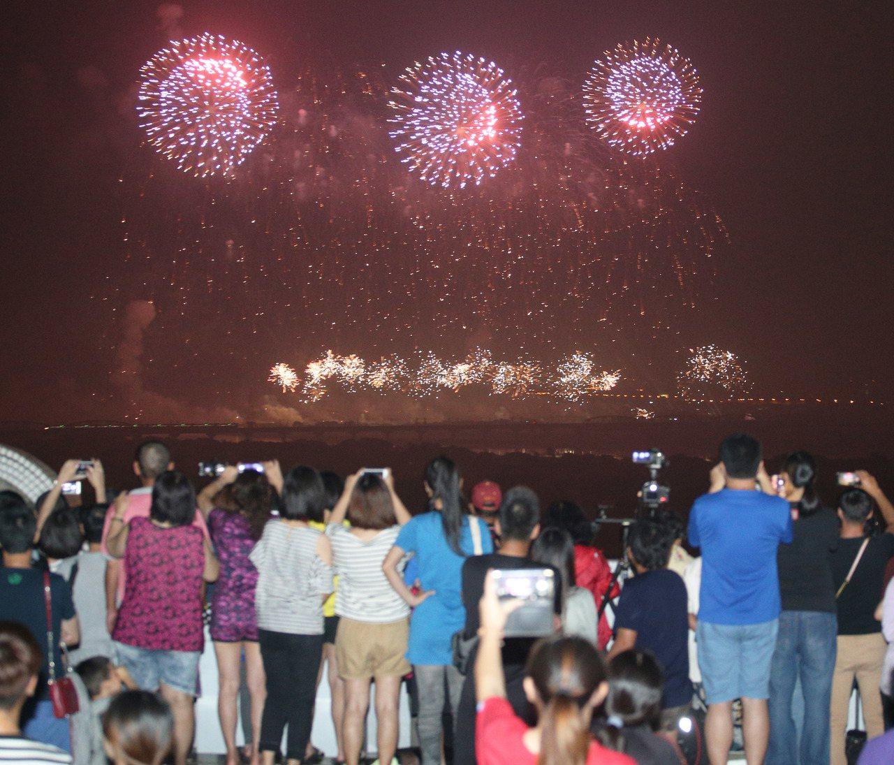 國慶焰火在高屏溪屏東河濱公園施放,長達42分鐘,璀璨煙火在高屏夜空綻放,讓上萬民...