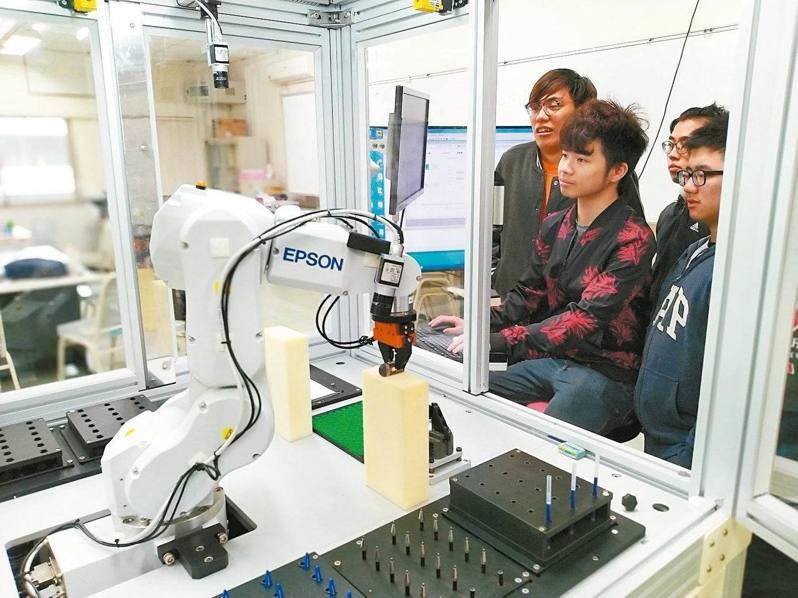 人工智慧時代來臨,產學界對AI人才需求殷切,多所大學增設人工智慧相關系所,圖為學生在校園裡操作智慧製造機械手臂等尖端設備。 圖/聖約翰科大提供