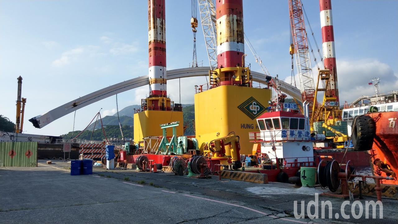 跨港斷橋的鋼梁已切除,但橋拱重300公噸,導致吊掛作業平台船二邊重量不平均,船艙...
