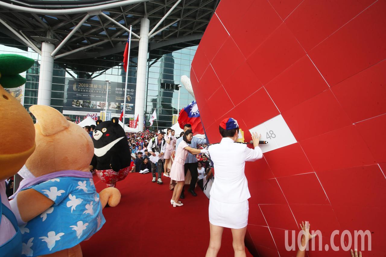 高雄市政府上午在高雄展覽館舉辦雙十國慶升旗典禮,現場湧進萬人,不過國旗背版一度掉...
