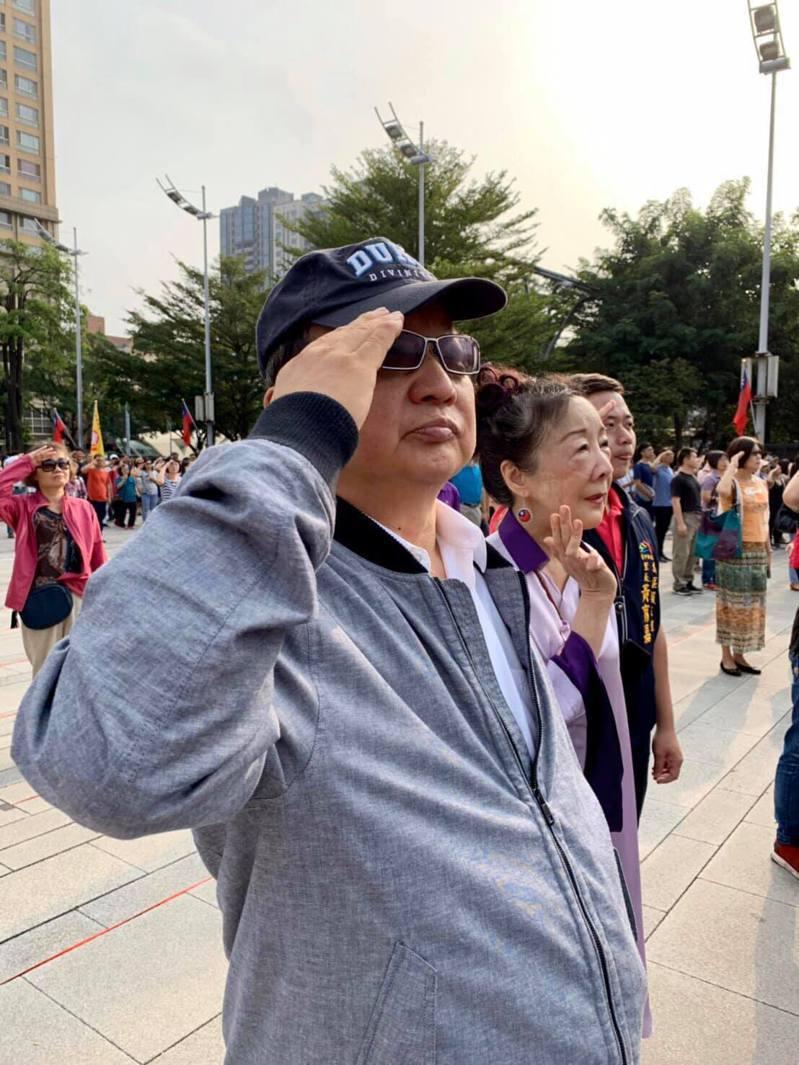 台中市前市長胡志強與夫人邵曉鈴今早參加國慶升旗,兩人站在人群中唱國歌,最後才被台上主持人「野生捕獲」,胡志強並未上台。圖/取自胡志強臉書