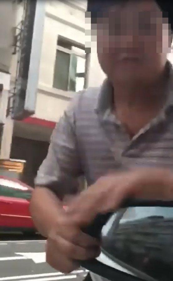 影片中拍下,男子徒手企圖扳開後照鏡,女駕駛嚇得俇按喇叭。圖/翻攝自「爆料公社」