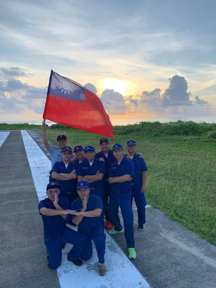 空軍駐太平島官兵,與國旗在晨曦中的跑道上合影。圖/取自空軍司令部臉書