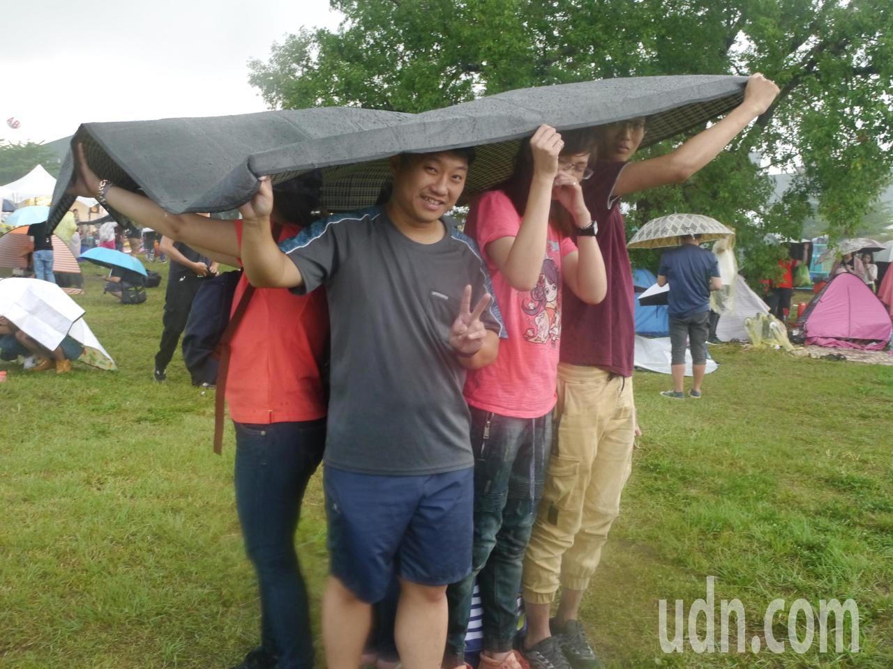 一群年輕人拿野餐地墊當雨具,以克難方式繼續聽歌。記者徐白櫻/攝影