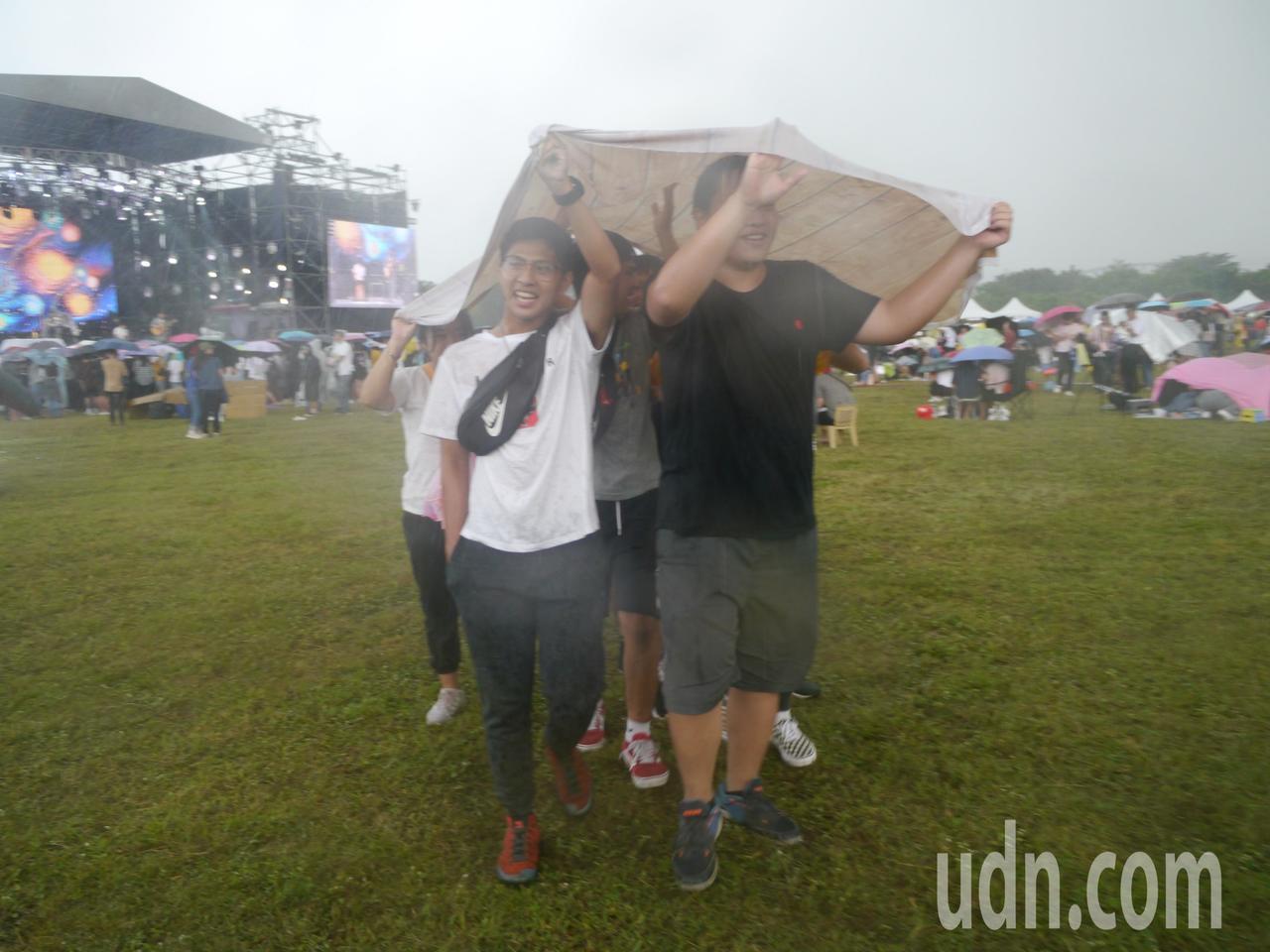 天際突然下起大雨突,野餐觀眾索性拿起野餐地墊當遮雨布。記者徐白櫻/攝影