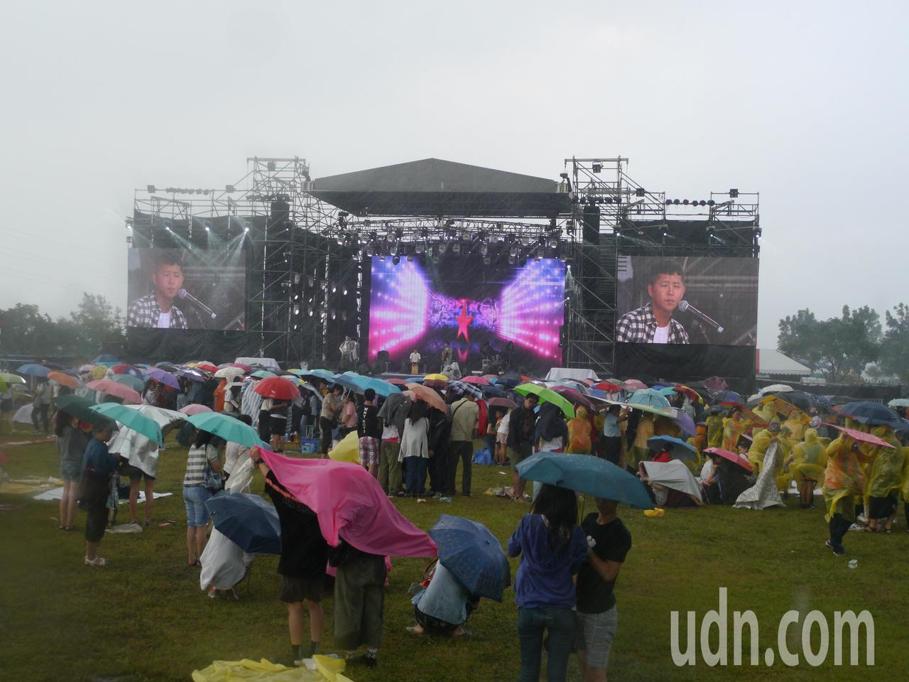 高雄大樹「舊鐵橋草地音樂會」開唱,突然下起大雨,仍有不少觀眾聚在舞台前聽歌。記者...